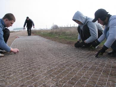 Участники субботника готовят сетку для ограждения